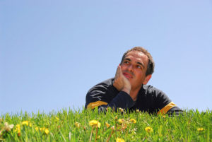 Smiling man lying on grass on background of blue sky, looking up